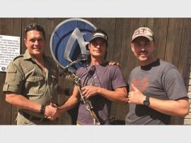 Johan Lottering and Redge Grant of Archer's Edge present the Tom Miranda signed Mathews bow to local archer, Jonathan Pentz.