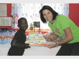 Joany-Ann Campher from Miki Maths holding up a birthday cake with Ayanda Ngwenya from eLollipop.