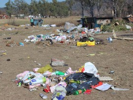 Rubbish is strewn across the grounds near the municipal skips in Hathorn Street.
