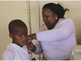 Darren Mtshali receives an immunisation shot from Ntombi Mnvulane.