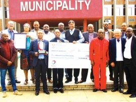 Holding the cheque are Endumeni Mayor S Richard Mbatha and Councillor Dr Sandy Bedassi.  From left:  Councillor S Zwane, acting Municipal Manager M Silinga, Councillor N Khanyile, Councillor C Carelse and Planning Manager Potsane. Back:  Councillor A Raubenheimer, Speaker Makhathini, Councillor L Khumalo, Councillor SB Mdluli, Councillor M Xaba, Councillor T Mahaye, Councillor T Zitha and Technical Services Manager Cindi.