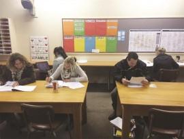 Teachers hard at work marking exam papers.
