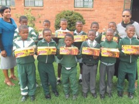 Miss Sishi and Miss Khumalo stand alongside some of the learners who received new school shoes.