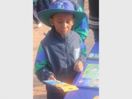 Gr. 0 Mitchell House learners, Kgethego Matloga, hands over the crayons she is donating for Mandela Day.