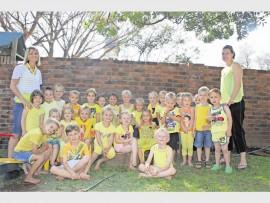 Monya Groenewald (Erica Pre-primêre Skool, skoolhoof) en Alexa de Jager (Erica Pre-Primêre Skool, onderwyser) saam met van die kinders wie geel aangetrek het ten bate van Kinderkanker Bewusmakingsmaand.