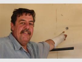 Danie Janse van Rensburg is tydens 'n huisaanval in die hand geskiet.  Hier wys hy waar die koeël wat waarskynlik vir sy vrou bedoel was, in die muur vasgeslaan het.