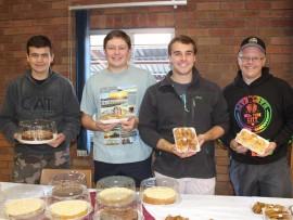 Pieter-Jan Gouws, Martin du Plessis, Jean-Pierre Viljoene en WJ Vos verkoop koeke tydens SAVF se mini-basaar.