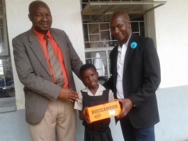 Mosengwa Chuma (Kanana Primary School principal) and Vuledzani Mashie (Old Mutual Seshego sales branch manager) hand over a pair of school shoes to Kedibone Makgoka, during the school shoes hand-over ceremony on Friday.