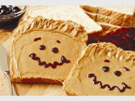 Peanut butter spread on bread and decorated with chocolate smiley faces will encourage many children to enjoy their lunch sandwiches.