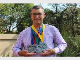 David Barnard proudly shows his medals he won in the four races he participated in around the world.