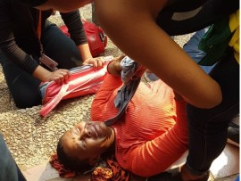 A student lays on the ground in hopes of gathering her bearings after having been fired with teargas PHOTO: Neo Phashe