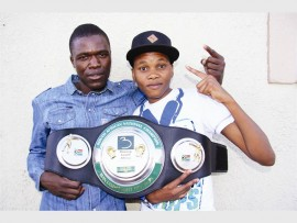 The South African female bantamweight champion, Bukiwe Nonina and her trainer, Emmanuel Mutavhatsindi show off her  champion belt.