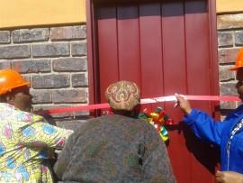 CoGHSTA MEC, Makoma Makhurupetje, Sarah Ngobeni and Mopani Mayor, Nkakareng Rakgoale prepare to cut the ribbon to officially hand over their new house to the Ngobeni family.