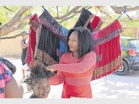 Ntsako Maluleke at her outdoor salon attending to her friend, Vinoliah Mabasa's hair.