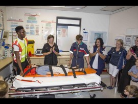 Pupil, Noah de Beer is the guinea pig in the stretcher for the IPSS Volunteer, who is applauded by Dr Bianca Visser, Murray Rait, Anneline Moodley, Tarryn Tucker, Trunelle Smith, Dino Bezuidenhout and Troy Potgieter