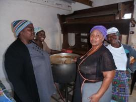 Melody Mokena, Nompumelelo Mokoena, Muriel Zungu and Phumzile Mkhize, serving from a huge pot of samp.