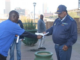 Councillor Bongani Nkwanyana habdiover a memorandum to Jeppe Police Station Commander Govandsamy Mariemuthoo.