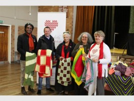 Sebastian Solomon, Lynton Lefevre, Kate Rivers, Judith Claire and Chris Boyd stand with knitted blankets and squares for the 67 Blanket Drive for Nelson Mandela Day