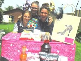 Estee Zwick, Tali Abrahamson and Sara Malka Fox wave their masks and prepare Purim gifts.
