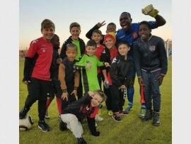 Highlands Park goalkeeper Tapuwa Kapini (blue shirt) celebrates with junior team players.