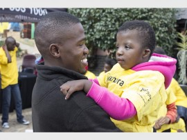 Elly Majola of Zinto spends time with a disabled child at Sithandiwe Disabled Care Centre in Lombardy East as part of a Mandela Day commemoration.