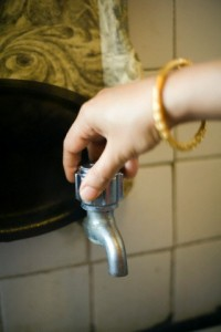 India - New Delhi - A woman turns on her tap to find it dry