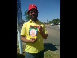 """Author Ashley """"Yabadaka"""" Mapokgole in Mamelodi with the book by different authors. Photo Supplied."""