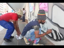 SIbusiso Ngwenya and Siyabonga Ndlame painting the wall to honour women. Photo: Thato Mahlangu.