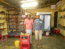 Sala Uddin (31) and Ashan Ullah (53) inside their shop that was looted by protesters. Photo: Mapula Moumakwe