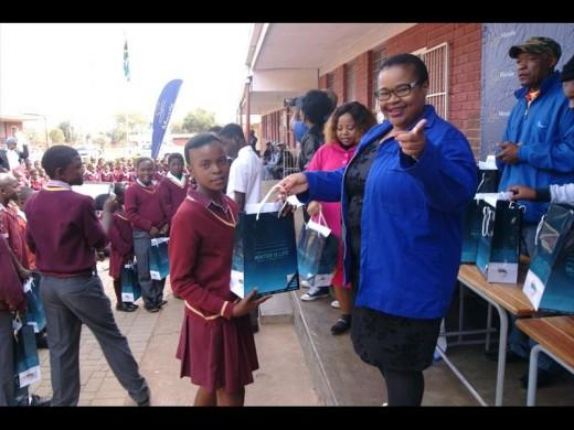 Zimasa Socikwa hands over a shoes and socks to a pupil.