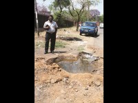 Pastor Gopaul Doresamy standing in front of the giant pothole in Court Street.
