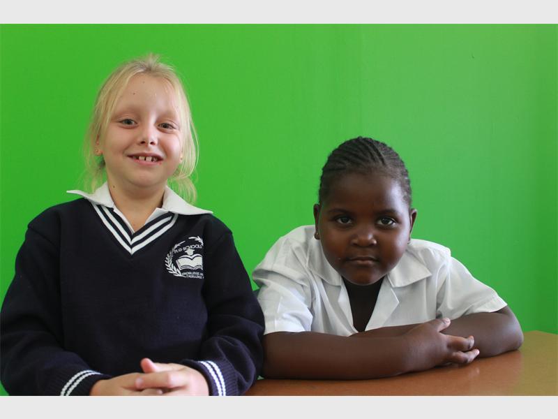 Kiara Kannemeyer and Nkazimulo Dube are seated in class.